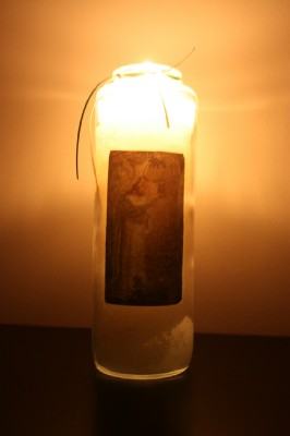 tall candle in glass with Jesus on the front.